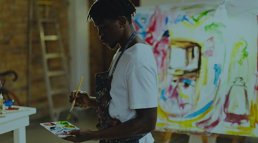 A Black male artist readies his palette of paints